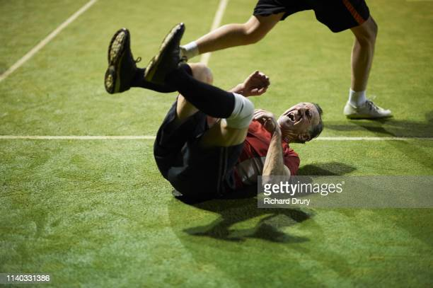 senior man playing soccer - lying down photos et images de collection