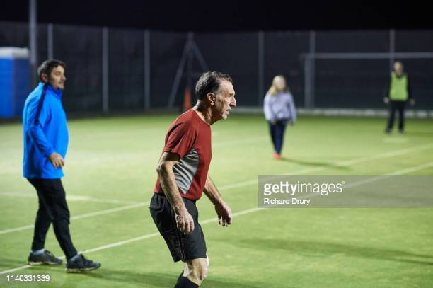senior man playing soccer with a mixed-age and gender group of friends - richard drury stock pictures, royalty-free photos & images