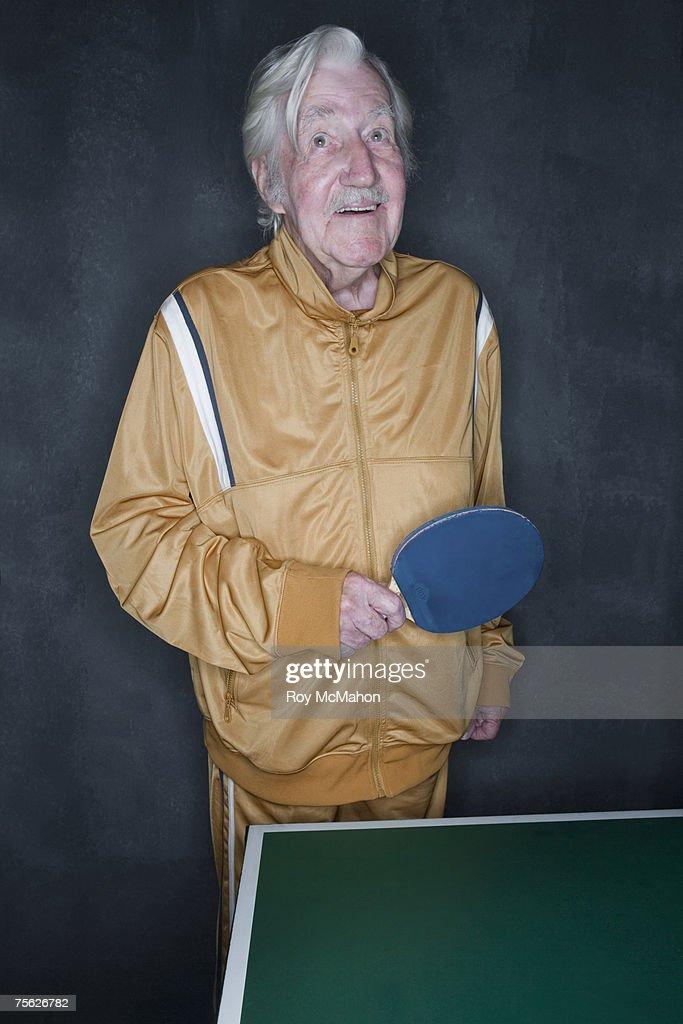 Senior man playing table tennis, upper half : Stock Photo