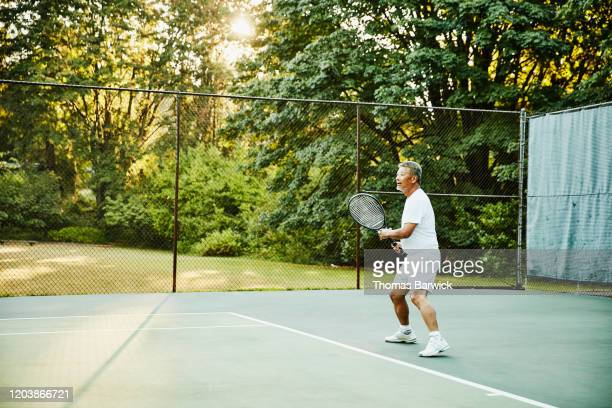 senior man playing tennis during early morning match - wellness stock pictures, royalty-free photos & images
