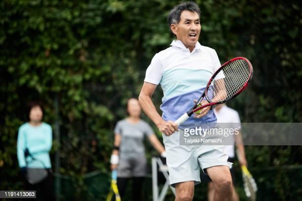 senior man playing tennis seriously - 気が若い ストックフォトと画像