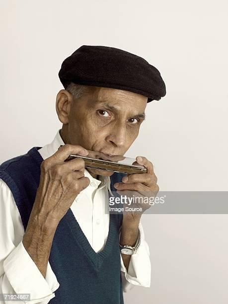 Senior man playing the harmonica