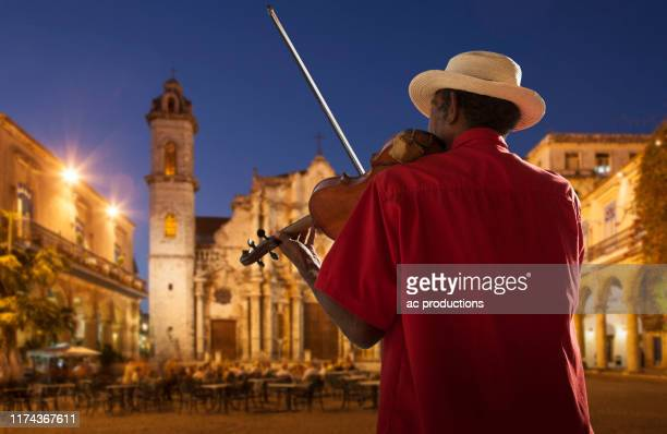 senior man playing violin at night in plaza de la catedral, havana, cuba - old havana stock pictures, royalty-free photos & images