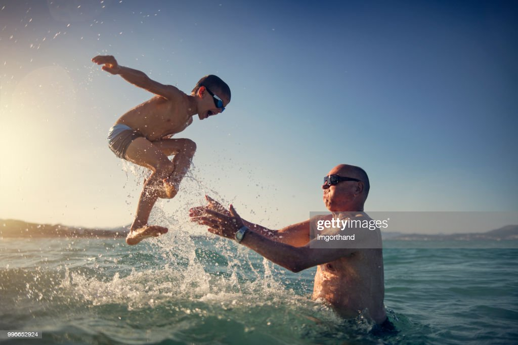 Senior man playing with grandson in sea : Stock Photo