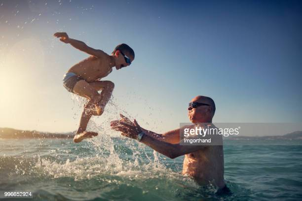 senior man playing with grandson in sea - vitality stock pictures, royalty-free photos & images
