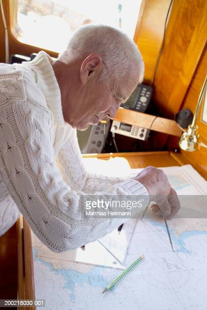 Senior man plotting chart on yacht, close-up