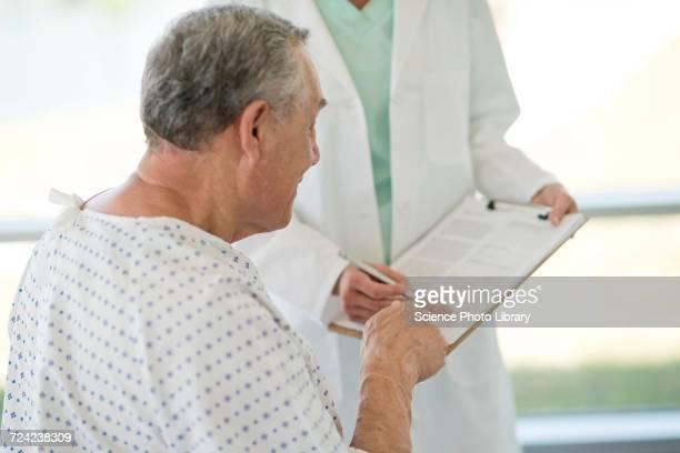 Senior man pointing at medical notes in hospital
