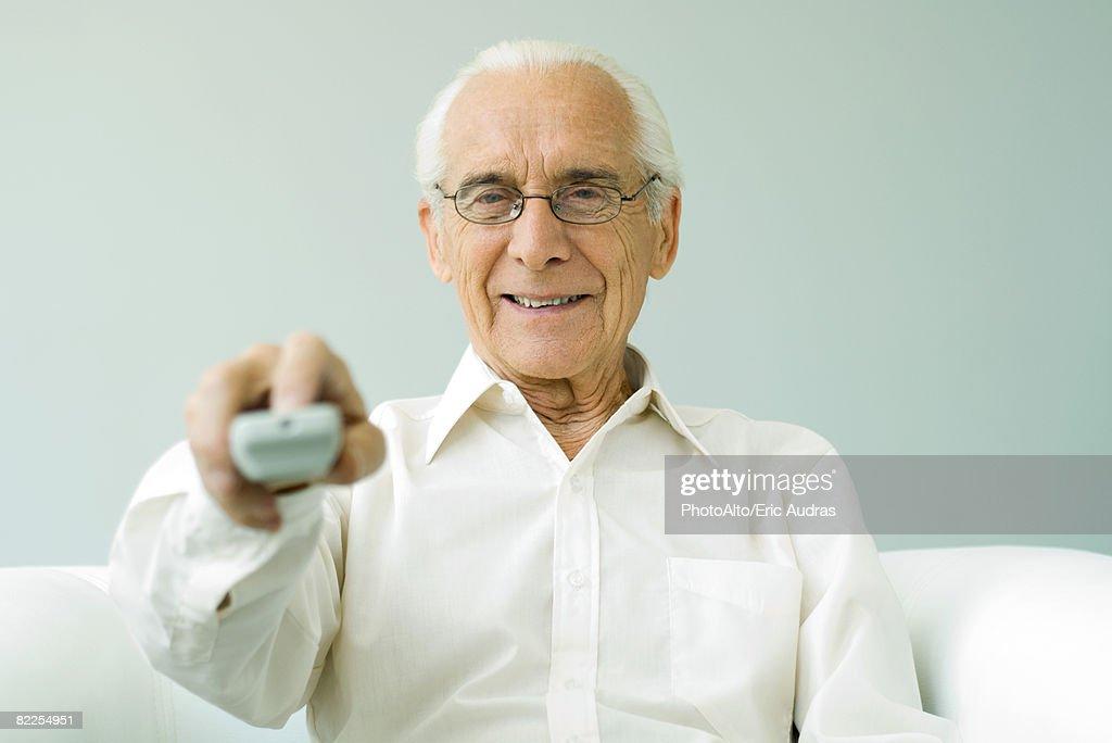 Senior man pointing remote control at camera, smiling : Stock Photo
