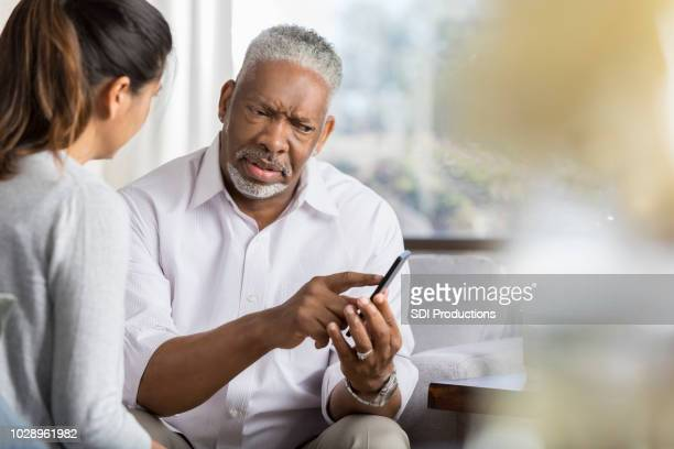 senior man points at something on smartphone - confused stock pictures, royalty-free photos & images