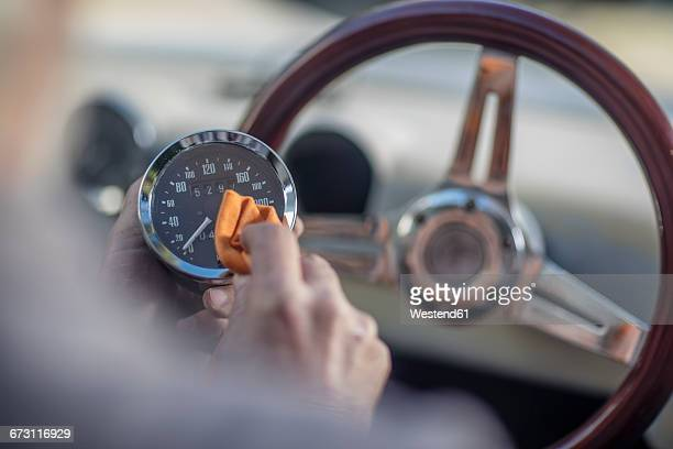 Senior man polishing tachometer of a car