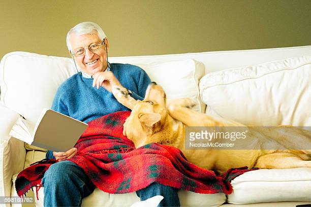 Senior man portrait laughing as dog asks for stroking