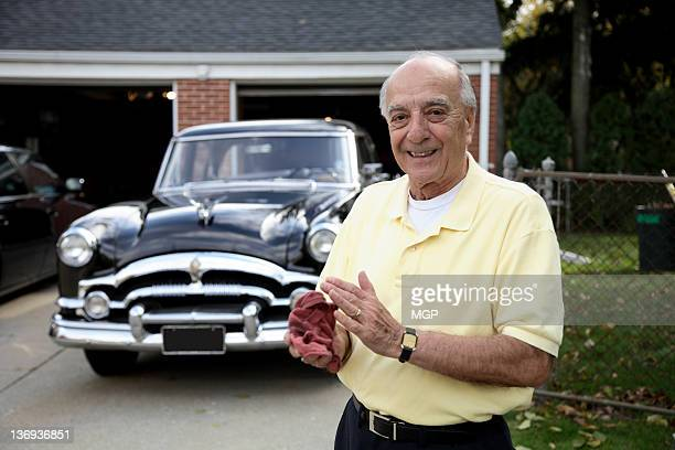 Senior man poses with vintage car