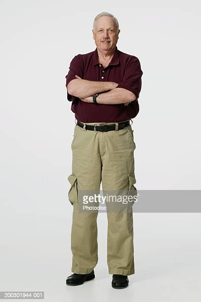 senior man posing in studio with arms crossed, portrait - cargo pants stock photos and pictures
