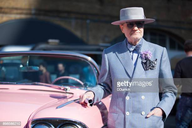 senior man posing with his pink 1960 cadillac - 1960 stock pictures, royalty-free photos & images