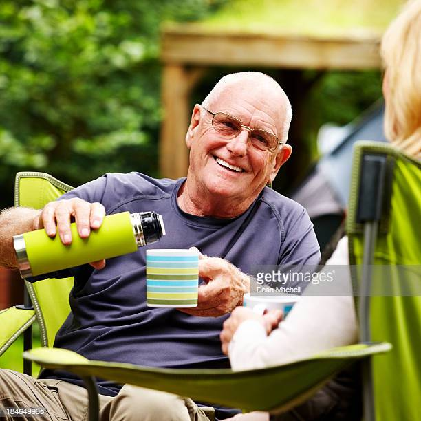 Senior Man Pouring Coffee While Camping