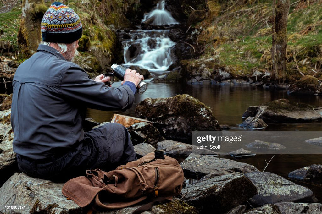 Senior man pouring from a thermos flask : Stock Photo