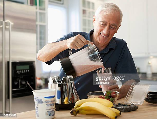 Senior homme verser le verre smoothie de fruits frais