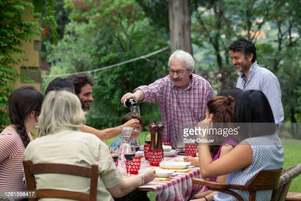 senior man pouring wine at family meal - mediterranean culture stock pictures, royalty-free photos & images