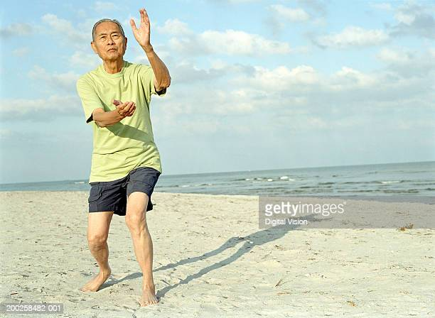 Senior man practicing tai chi on beach