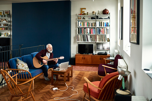 Senior man practising guitar at home in retro living room - gettyimageskorea