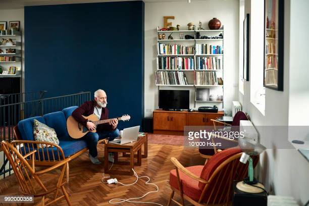 senior man practising guitar at home in retro living room - freizeitaktivität stock-fotos und bilder
