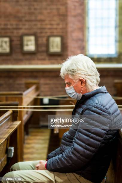 senior man praying in church wearing protective face mask with social distancing - christianity stock pictures, royalty-free photos & images