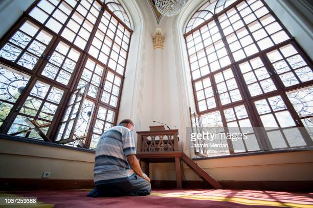 senior man praying in mosque - jasmin lord stock-fotos und bilder