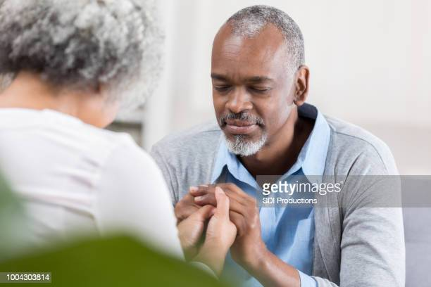 senior man prays with wife at home - black people praying stock pictures, royalty-free photos & images