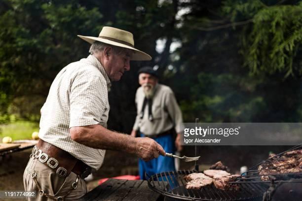 senior man preparing barbecue - cultura argentina imagens e fotografias de stock