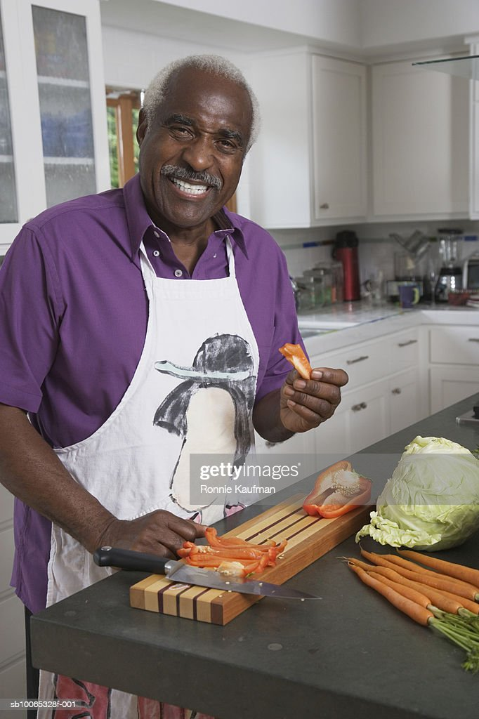 Senior man preparing food in kitchen, smiling : Foto stock