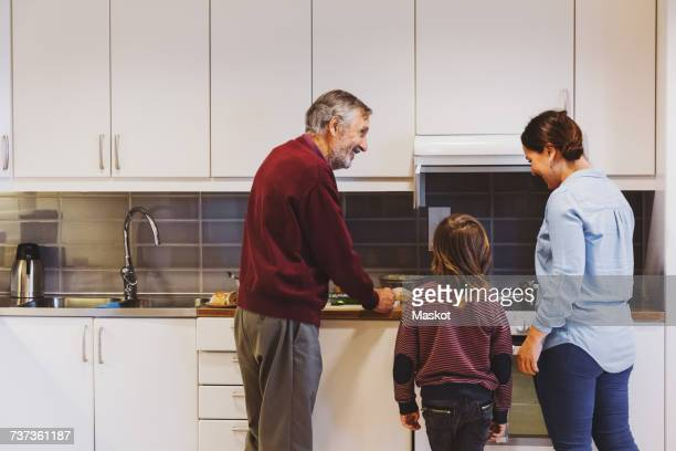 Senior man preparing food with great grandson and daughter in kitchen