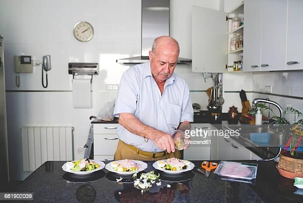 Senior man preparing salad in the kitchen