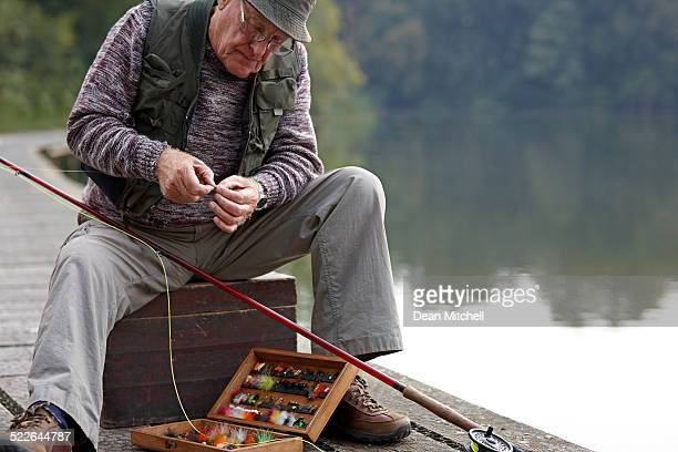 senior man preparing the bait for fishing - fishing industry stock pictures, royalty-free photos & images
