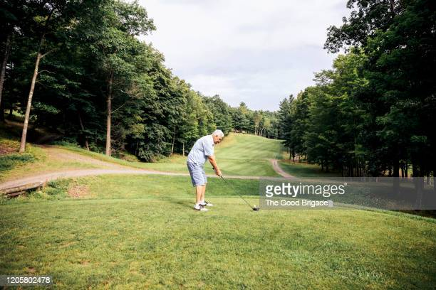 senior man preparing to hit tee shot - golftee stock-fotos und bilder