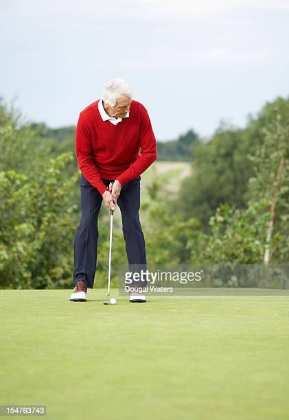 senior man preparing to putt ball on golf course. - einlochen golf stock-fotos und bilder