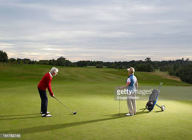 senior man preparing to tee off on golf course, - golf stock pictures, royalty-free photos & images