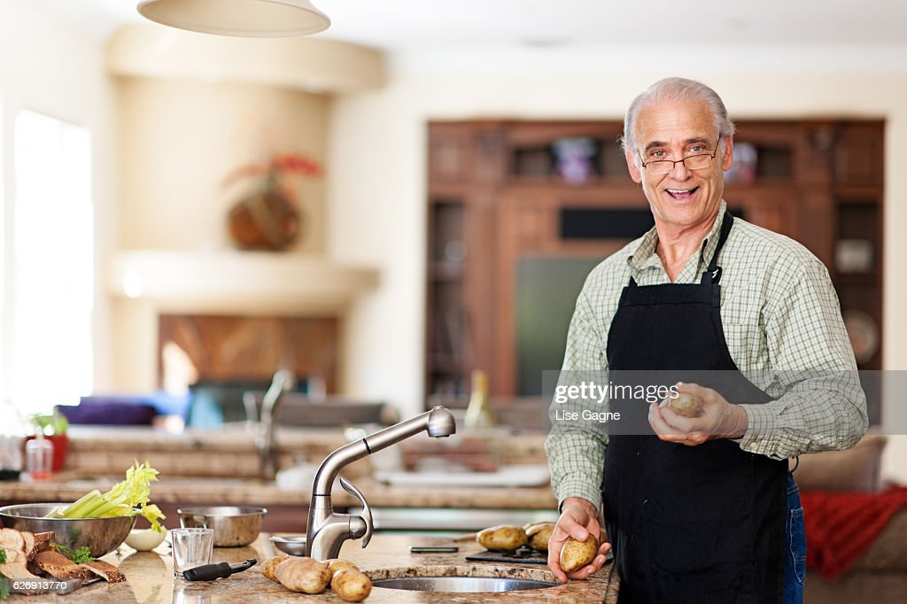 Senior man preparing to wash potatoes : Stock Photo