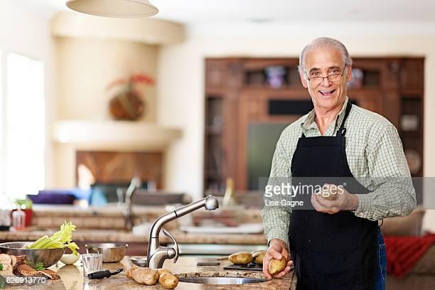 Senior man preparing to wash potatoes