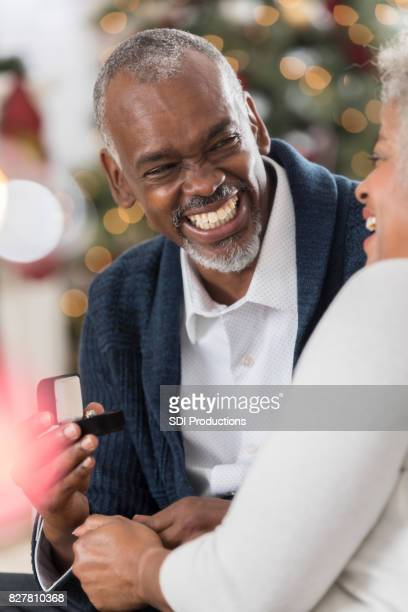 senior man proposes on christmas day - engagement ring box stock photos and pictures