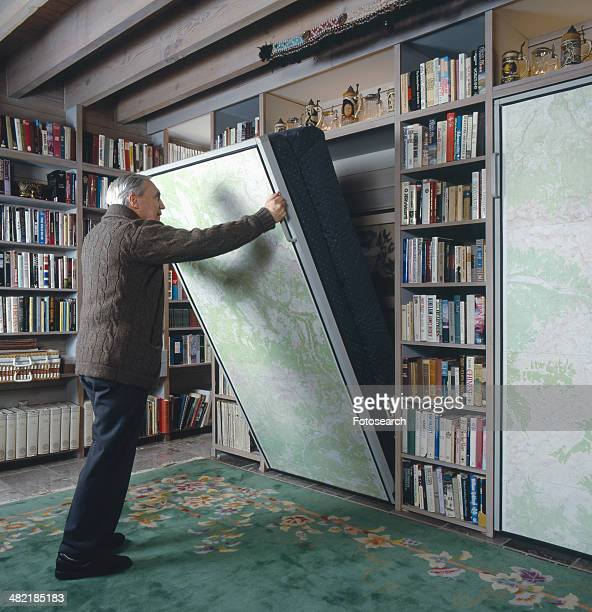 Senior man pulling Murphy bed in library of a traditional house