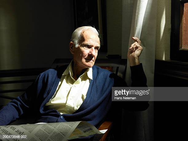Senior man pulling shade back from window