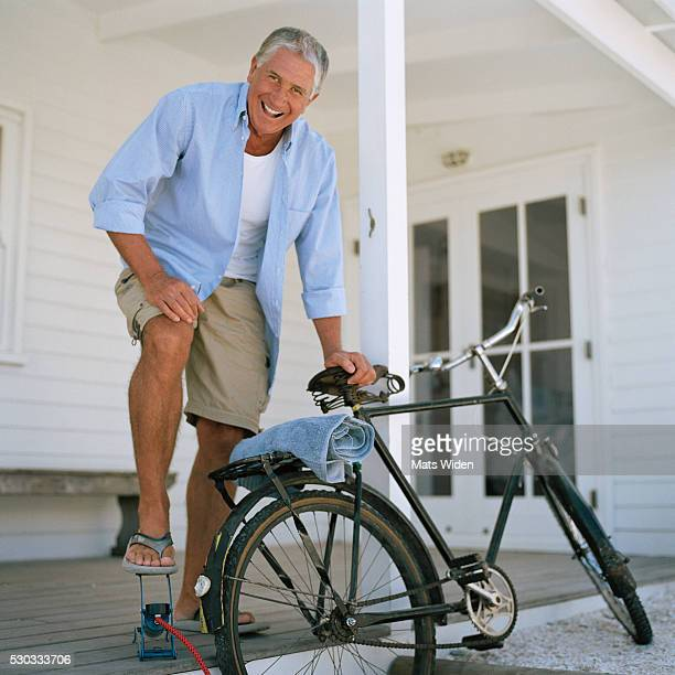 senior man pumping up a bicycle - shorts stock pictures, royalty-free photos & images