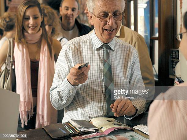 senior man purchasing ticket at theatre box office - hygiaphone photos et images de collection