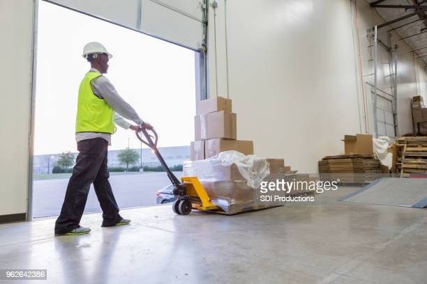 senior man pushes load of boxes on dolly - loading dock stock pictures, royalty-free photos & images