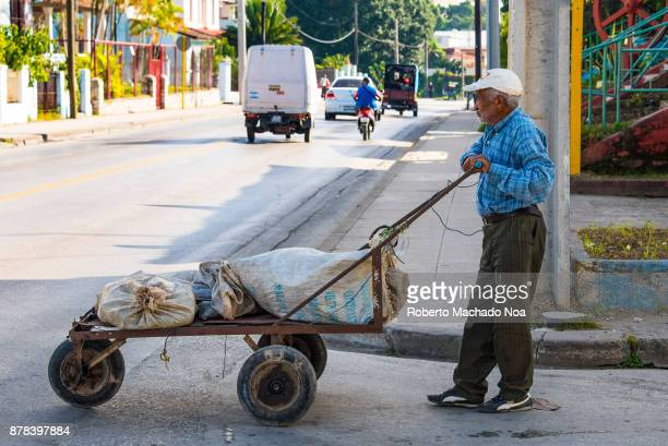 Senior man pushing a cart with sacks full of aluminum cans and bottles for recycling The Cuban government pays per collected items and per kg