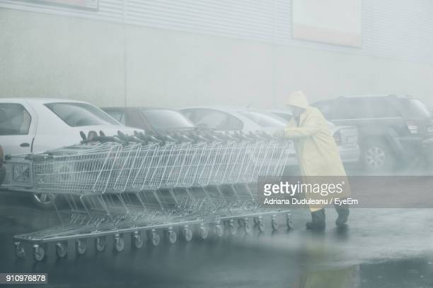 senior man pushing shopping cart while walking on street during rainfall - extreme weather stock photos and pictures