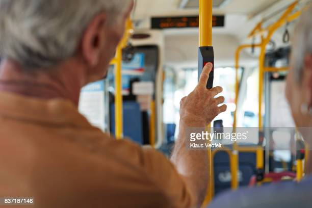 Senior man pushing 'stop' button inside public bus