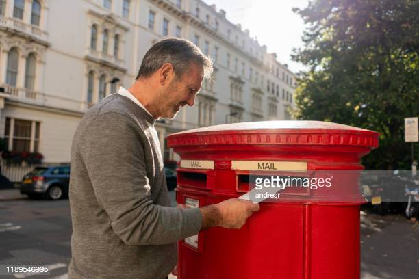 senior man putting a letter in the mail - message stock pictures, royalty-free photos & images