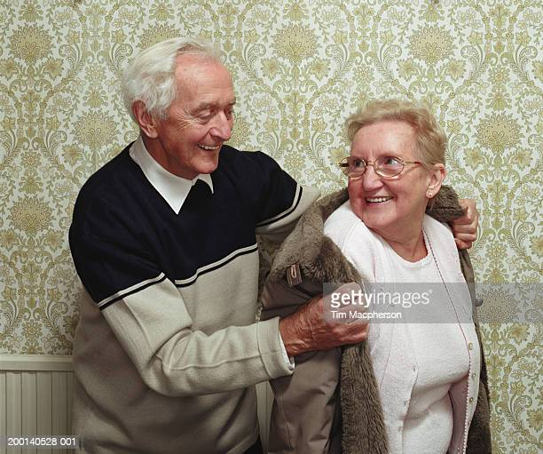 Senior man putting coat on senior woman