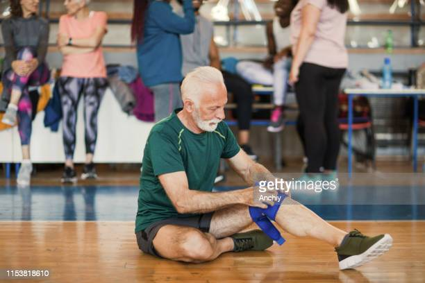 senior man putting kneepad on before dance class starts - padding stock pictures, royalty-free photos & images